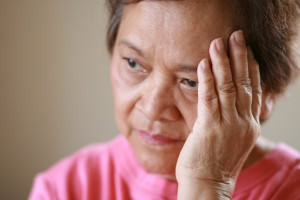 Elderly Asian woman with a worried look on her face, shallow depth of field with focus on hand.